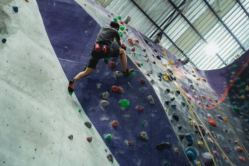 Low angle back view of unrecognizable sportsman climbing wall with holds while practicing alpinism under roof