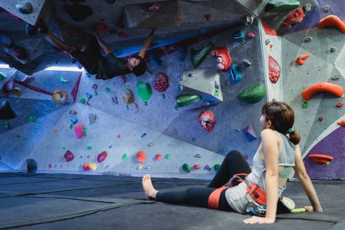 Unrecognizable female mountaineer in sportswear resting on floor under fit ethnic male friend climbing wall with grips