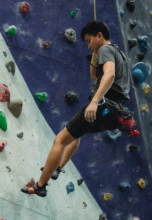Asian male climber ascending artificial rock during training