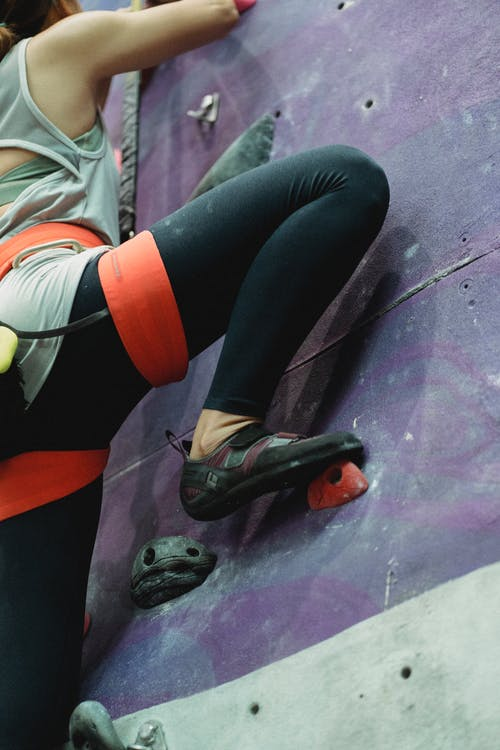 Crop mountaineer climbing wall with holds during training