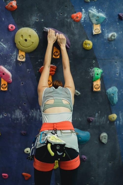 Unrecognizable climber ascending artificial rock during training
