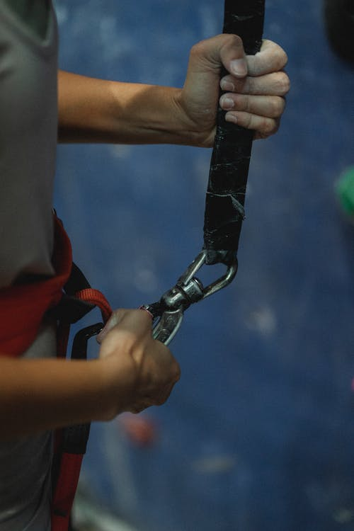 Side view of crop anonymous fit female alpinist with harness preparing to practice extreme sport near climbing wall