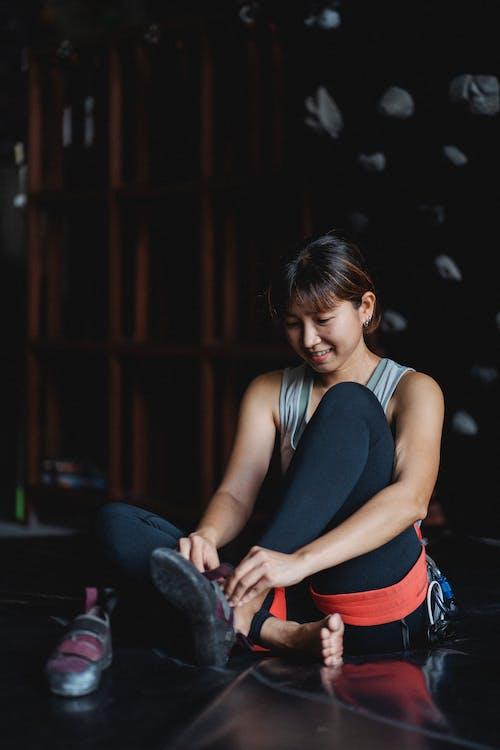 Asian sportswoman preparing for training in climbing gym