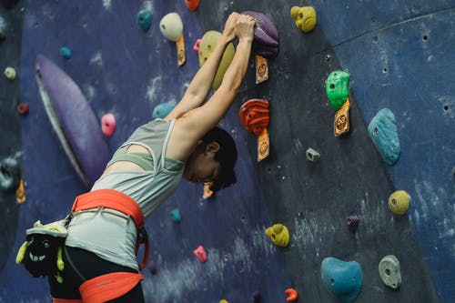 From below of focused female climber in activewear standing near climbing wall and stretching before training in gym