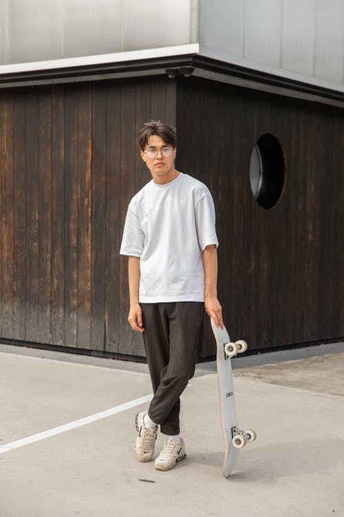 Full length of confident young Asian guy in white t shirt and eyeglasses leaning on skateboard while standing in city park after workout