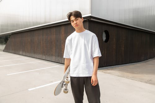 Confident young Asian man standing near modern building with skateboard in hand