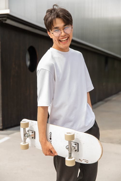 Joyful ethnic male teenager carrying skateboard and laughing after training in park