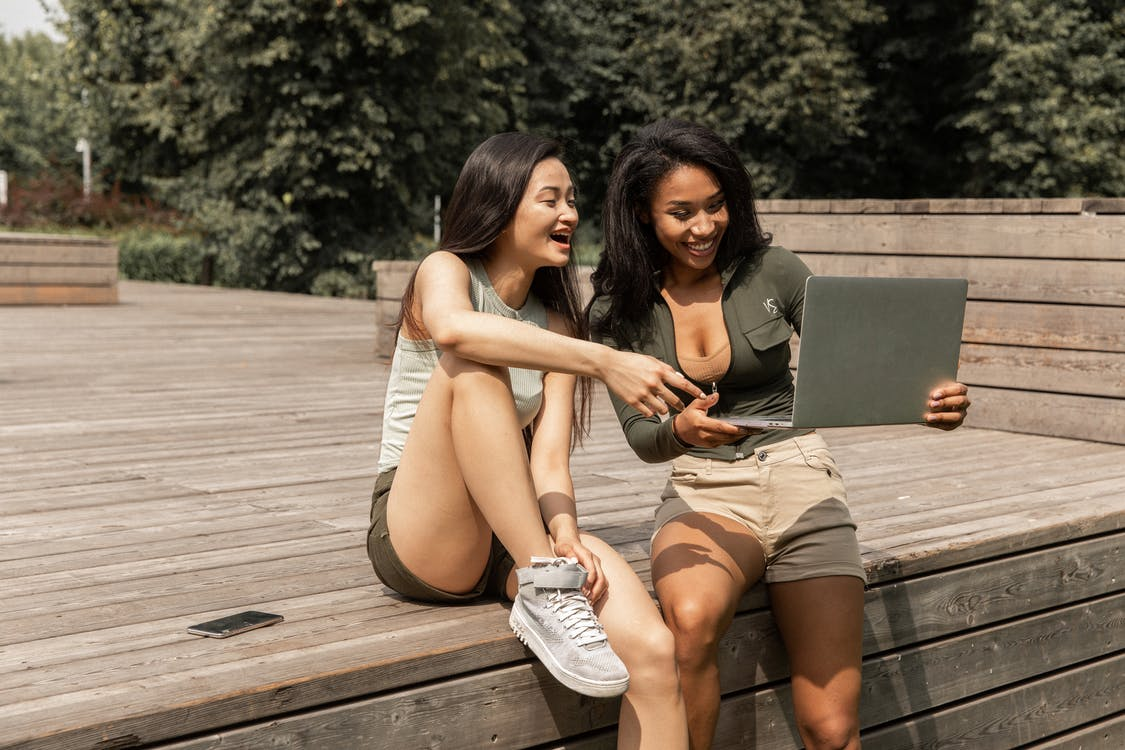 Happy young multiracial female friends in casual clothes laughing while watching funny video on laptop sitting on wooden podium in park