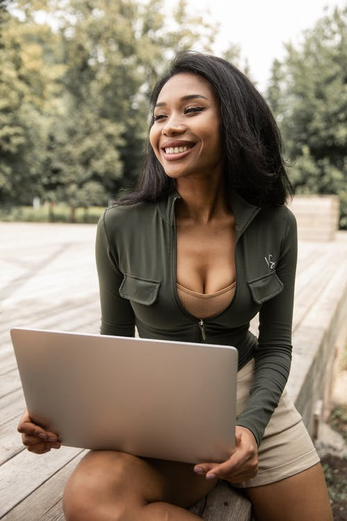 Cheerful young Hispanic female blogger using laptop in park