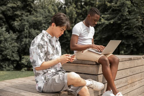 Busy young diverse men browsing laptop and smartphone in green park