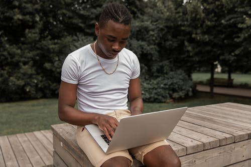 From above of attentive young black male freelancer with Afro braids in casual outfit typing on laptop while working distantly sitting on wooden bench in green park