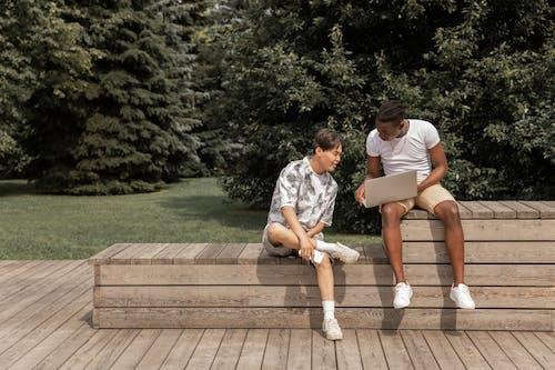 Jeune Homme Noir Montrant Un Ordinateur Portable à Un Ami Ethnique Assis Sur Un Banc Dans Le Parc