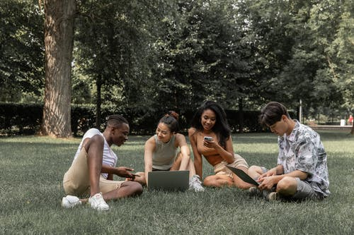 Group of diverse friends browsing laptops and mobile phone while spending time in park