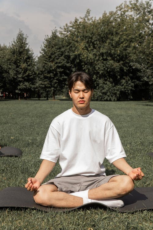 Full body of concentrated Asian male in casual wear sitting in Padmasana with closed eyes in summer park