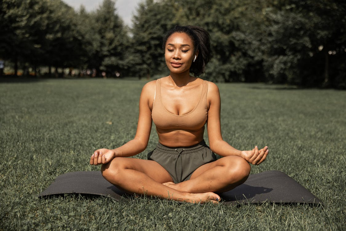 Fit ethnic woman practicing yoga in park