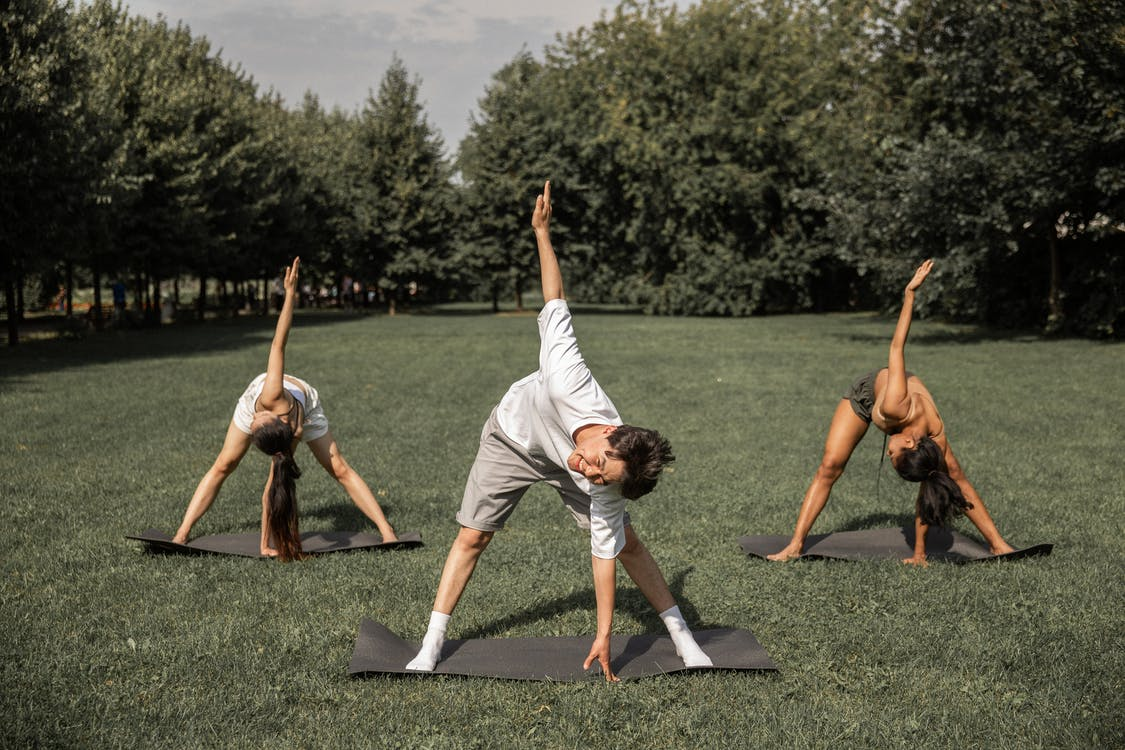 Group of diverse friends doing Revolved Wide Legged Forward Bend while exercising yoga on lawn