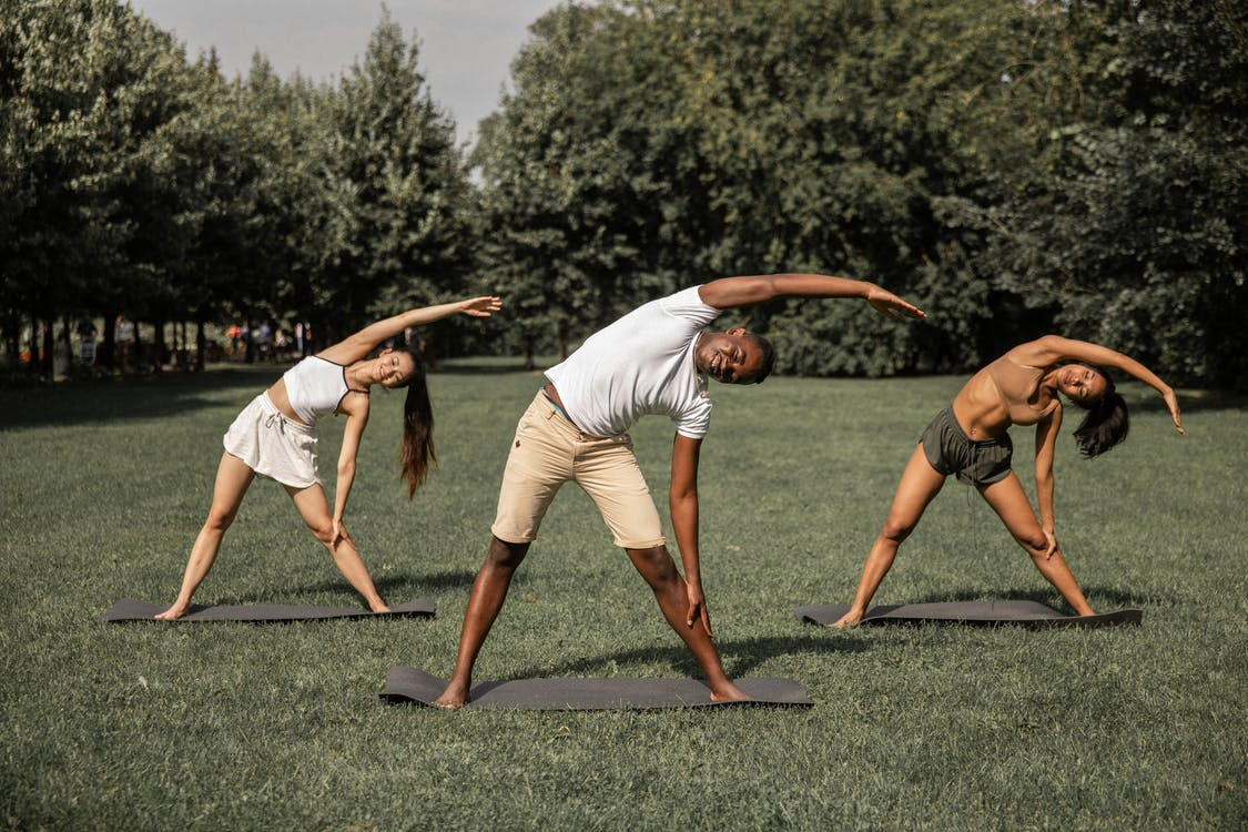 Group of diverse people in activewear stretching body while practicing Parivrtta Trikonasana in summer park