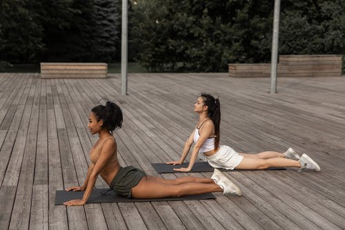 Side view of focused diverse girlfriends doing High Cobra pose while stretching bodies on wooden platform in park