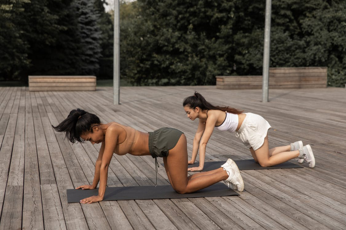 Fit women practicing Box pose together in nature