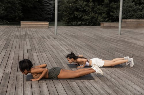 Fit women doing low push ups in nature