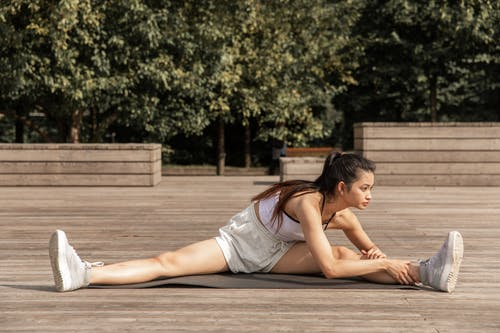 Young fit woman performing wide splits on mat