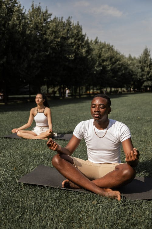 Full body of flexible barefoot couple in activewear sitting on mats in Lotus pose with closed eyes while practicing yoga together