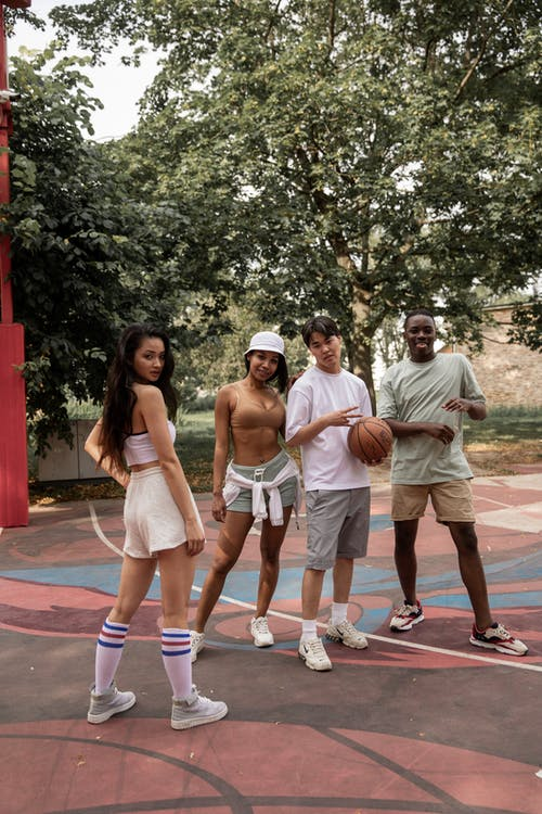 Group of multiracial friends in sportswear standing on basketball court with ball and looking at camera