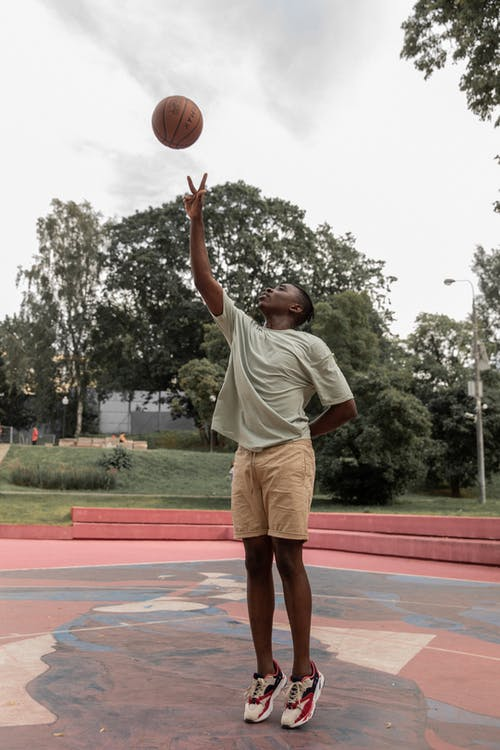 Black man playing basketball on court