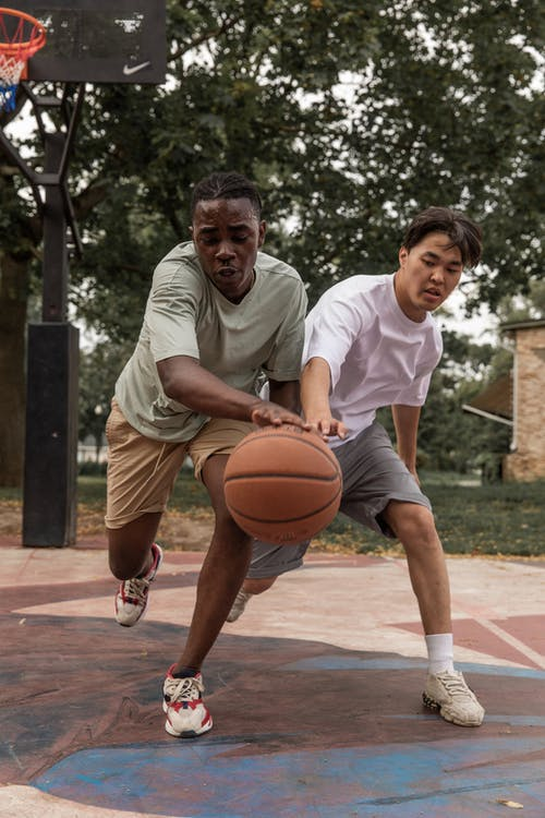 Confident multiracial players in sportswear competing for basketball ball while playing game on court