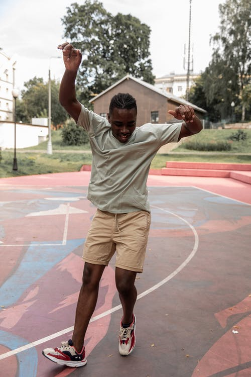 Full body joyful fit African American male in casual clothes dancing merrily with arms raised on sports ground on clear summer day