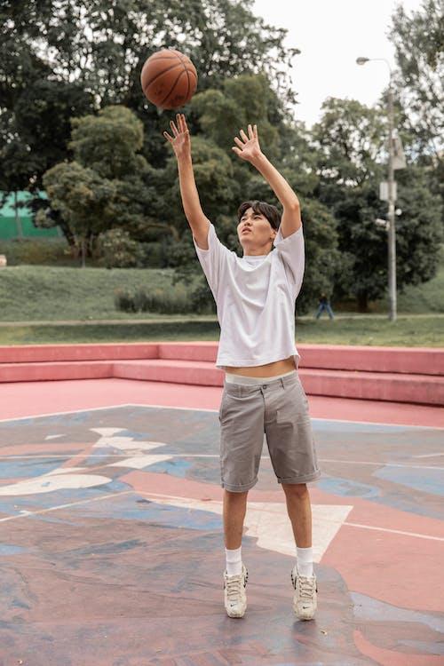 Asian man throwing basketball ball on sports ground