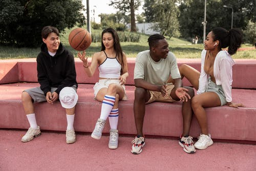 Full length happy young multiracial friends in casual wear sitting on pink stone bench with basketball ball in green park and chatting