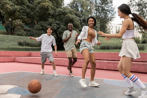 Delighted multiethnic friends playing basketball in park