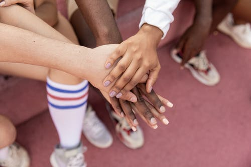 Faceless multiracial sport team stacking hands on court