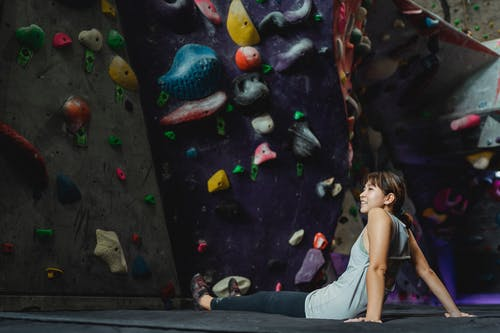 Side view of smiling Asian climber in activewear sitting on floor near climbing wall and looking away