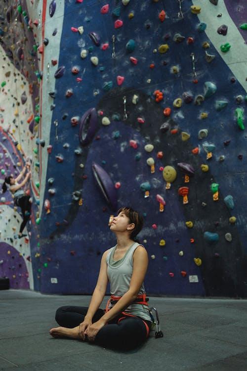 Calm female in sportswear sitting against climbing wall