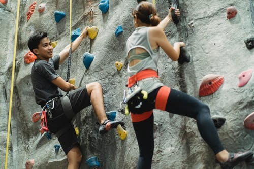 Sportspeople training on climbing wall in gym