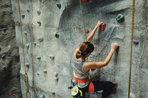 From above of anonymous female climber in activewear with special equipment climbing on climbing wall in gym