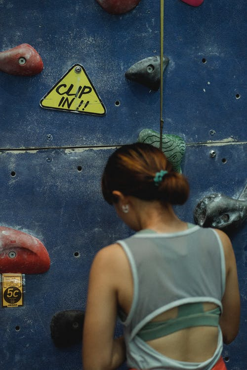 Back view of faceless female climber in sportswear preparing for clambering while standing near bouldering wall in gym
