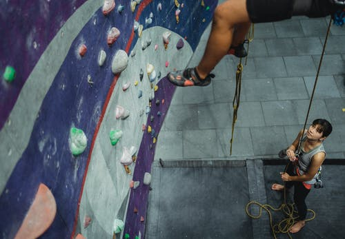 Concentrated Asian female athlete in sportswear holding rope while training with alpinist on climbing wall in gym