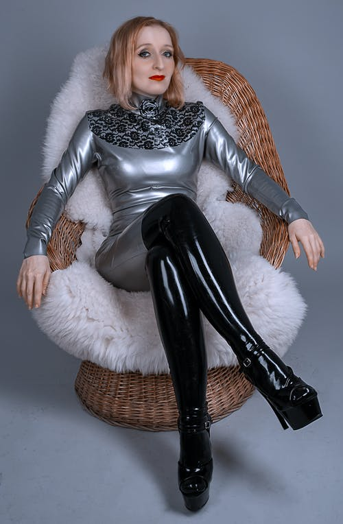 Woman in White Fur Coat and Black Stockings Sitting on Brown Wicker Chair