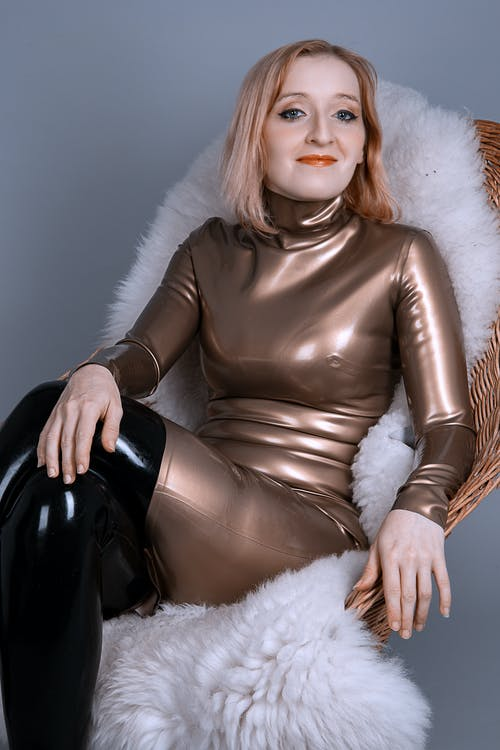 Woman in Black Leather Jacket Lying on White Fur Textile