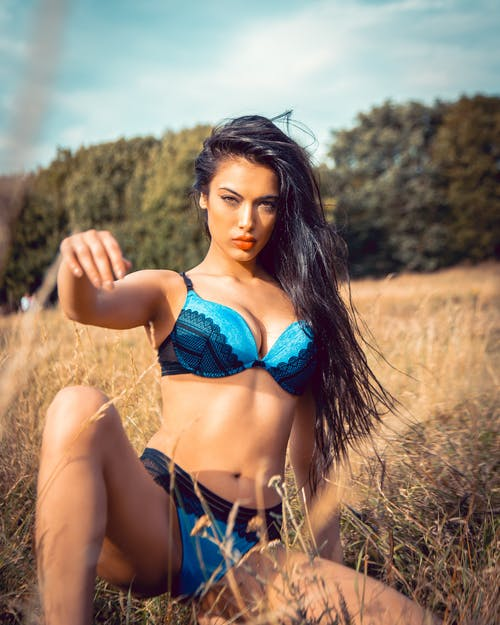 Woman in Blue Bikini Sitting on Brown Grass Field