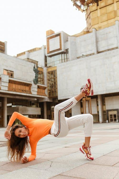 Woman in Orange Long Sleeve Shirt and White Pants Dancing