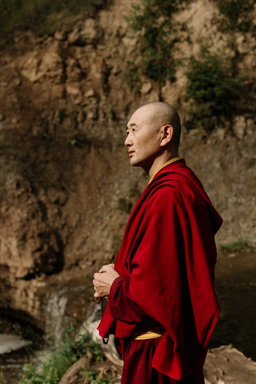 Man in Red Robe Standing Near Brown Wall