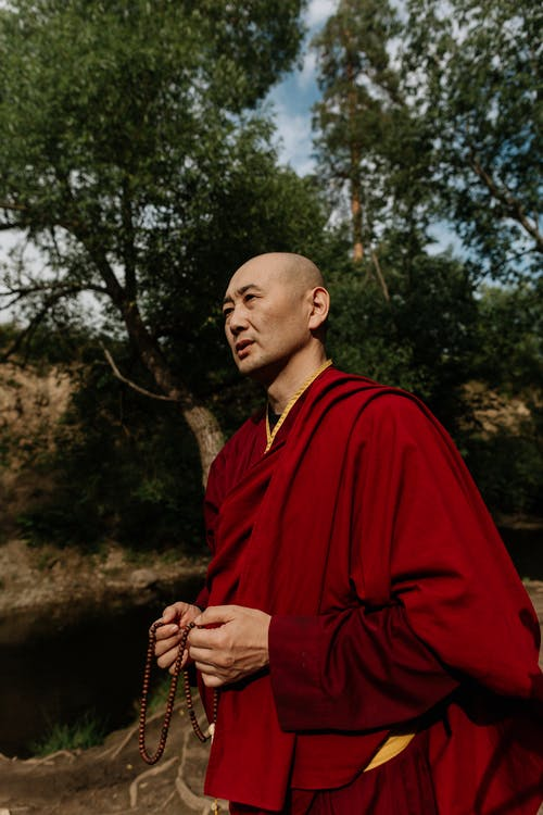 Man in Red Robe Standing Near Green Trees