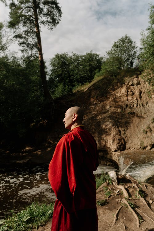 Man in Red Hoodie Standing on Rock Formation Near River