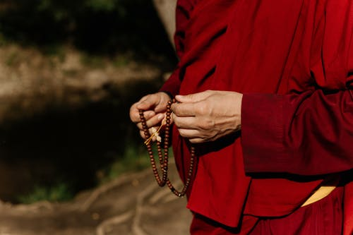 Person in Red Long Sleeve Shirt Holding Brown Beaded Necklace