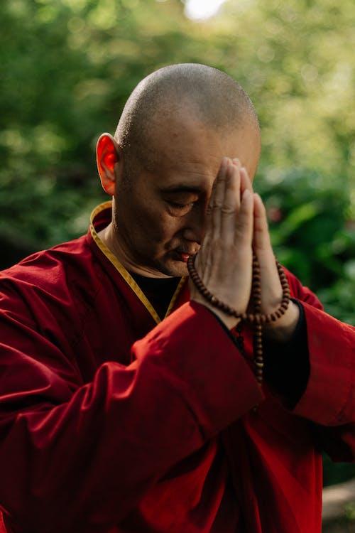 A Monk in Red Robe Praying