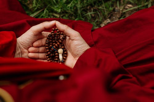 Person Holding Red and Black Beads